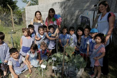 The master gardeners distribute among the boys the food they produce in the garden.