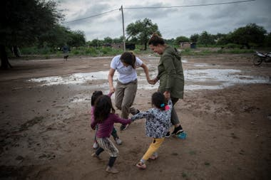 Two volunteers from the NGO Pata Pila play with children from the El Cañaveral community 1