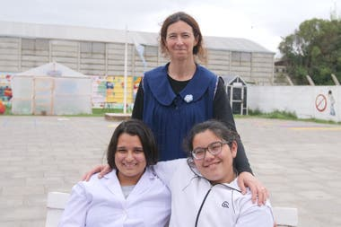 Claudia with the students Camila (today in 6th year) and Lourdes (who graduated this year), when LA NACION traveled to learn about the biodigester project