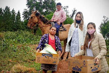 Claudia (black chinstrap) and Débora with a student and their mother who came to the school to look for food and content