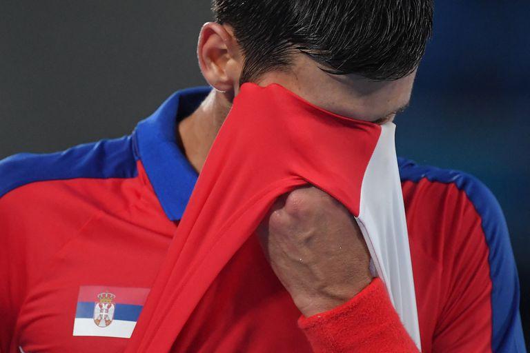 El serbio Novak Djokovic se limpia la cara mientras compite contra el alemán Alexander Zverev durante el partido de tenis de la semifinal masculina individual